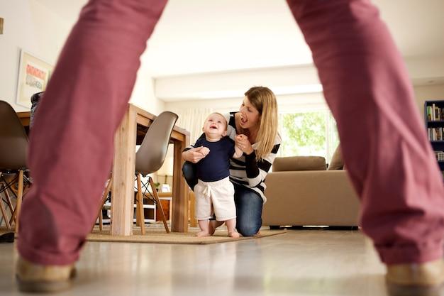 Mère et enfant sourient ensemble tout en apprenant à marcher