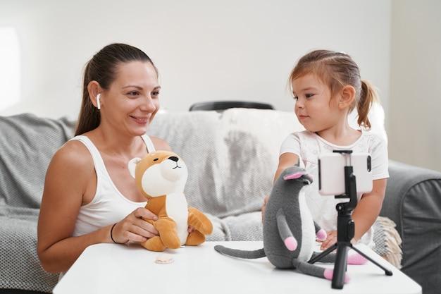 Mère avec enfant en streaming vidéo en ligne de jouets de déballage. profession d'influenceur, blog de maman. photo de haute qualité