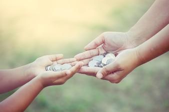 Mère et enfant tenant la pièce de monnaie dans les mains comme concept d'argent d'épargne dans le ton de couleur vintage