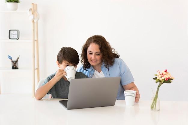Mère avec enfant travaillant sur ordinateur portable