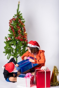 Mère et enfant très heureux avec cadeau un jour de noël et bonne année sur fond en studio
