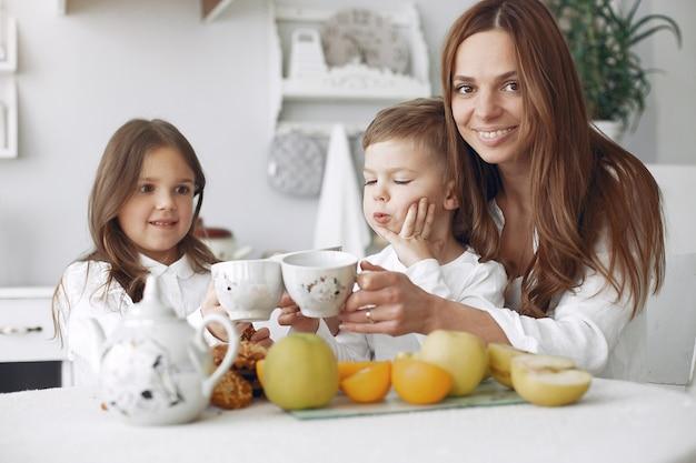 Mère avec enfants assis dans une cuisine et prendre un repas