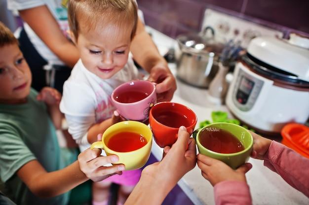Une mère avec des enfants boit de la compote à la cuisine, des moments heureux pour les enfants.