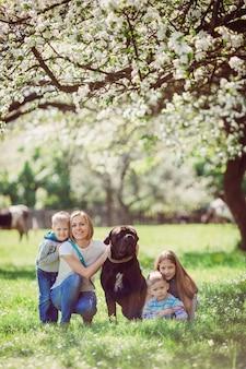La mère, les enfants et le chien assis sur l'herbe