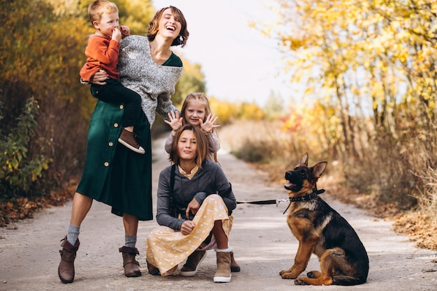 Mère avec enfants et chien dans un parc en automne