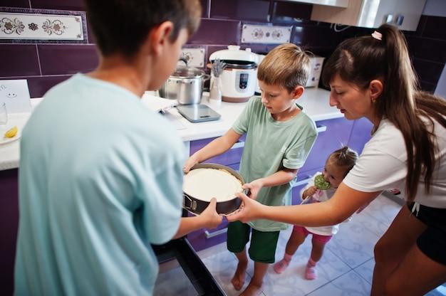 Mère avec enfants cuisinant dans la cuisine, moments heureux pour les enfants. gâteau au fromage au four.
