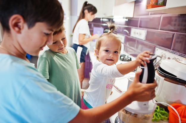 Mère avec enfants cuisinant dans la cuisine, moments heureux pour les enfants. travailler avec un mélangeur.