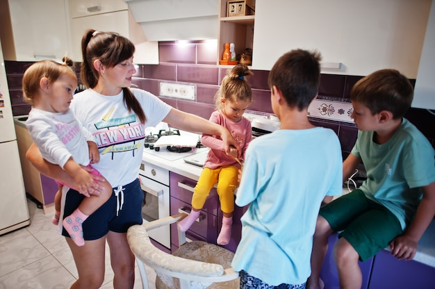 Mère avec enfants cuisinant dans la cuisine, moments heureux pour les enfants.