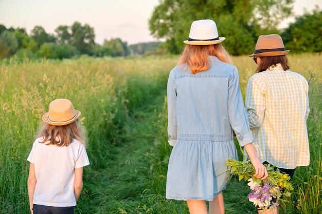Mère et enfants deux filles marchant le long d'une route de campagne à travers un pré. été, nature, famille, vacances
