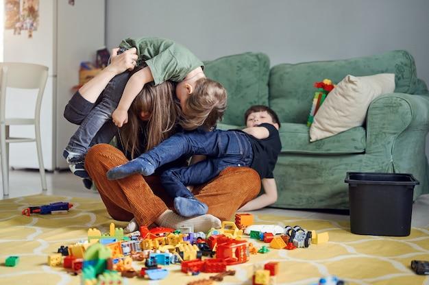 Mère avec enfants embrassant, s'amusant, riant à la maison. parent avec fils passant du temps ensemble