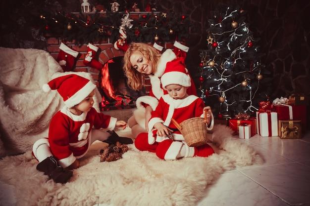 Une mère avec des enfants est assise près de la cheminée et joue avec des cônes - décorations de noël