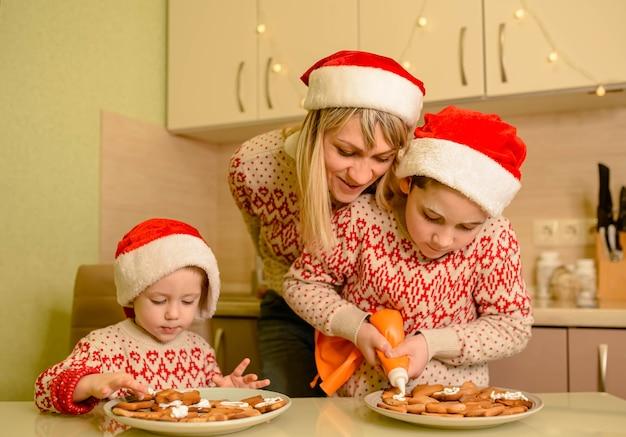 Mère et enfants faisant des biscuits en pain d'épice pour noël