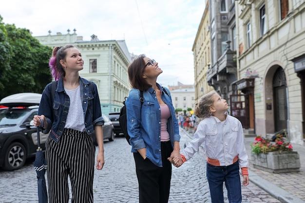 Mère et enfants filles adolescentes et plus jeunes marchant ensemble dans la rue de la ville et levant les yeux
