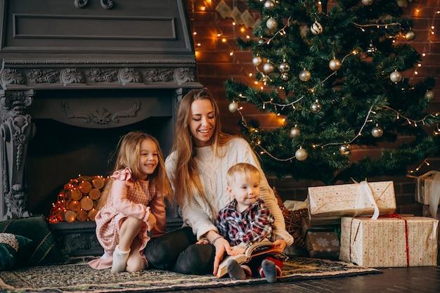 Mère avec enfants par sapin de noël