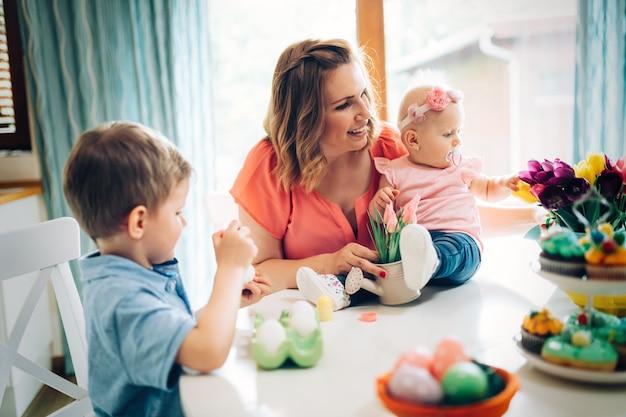 Mère et enfants peignant des œufs colorés. maman, tout-petit et enfant d'âge préscolaire peignent et décorent un œuf de pâques.
