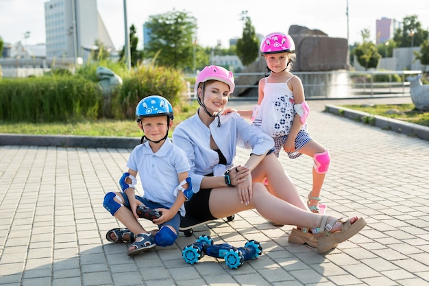 Une mère avec des enfants portant des casques s'assoit sur une planche à roulettes et joue dans le parc avec une voiture robot contrôlée par un gant.