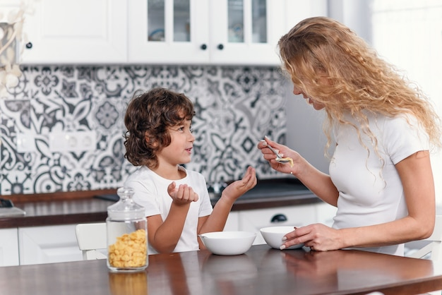 Mère et enfants prenant leur petit déjeuner à la maison