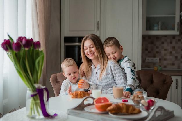 Mère avec enfants prenant son petit déjeuner dans la cuisine