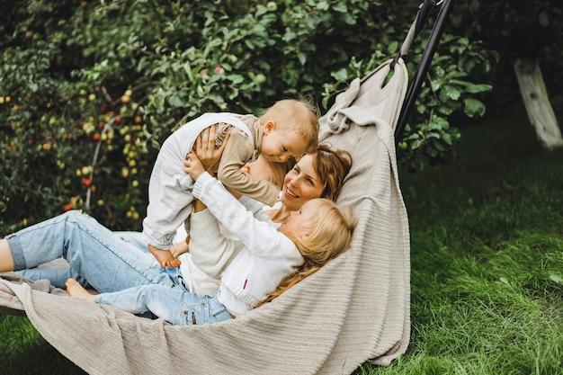 Mère avec enfants s'amusant dans un hamac. maman et enfants dans un hamac.