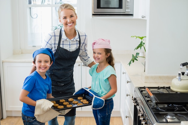 Mère et enfants tenant un plateau de biscuits cuits au four dans la cuisine