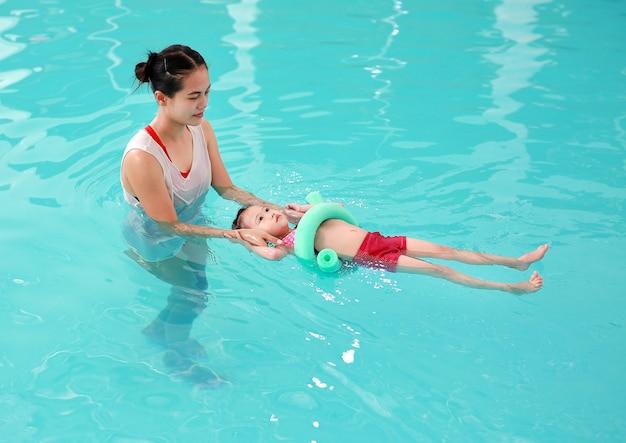 Mère enseignant enfant dans la piscine avec nouille en mousse