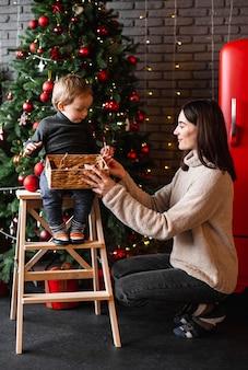 Mère enseignant à son fils comment décorer l'arbre de noël