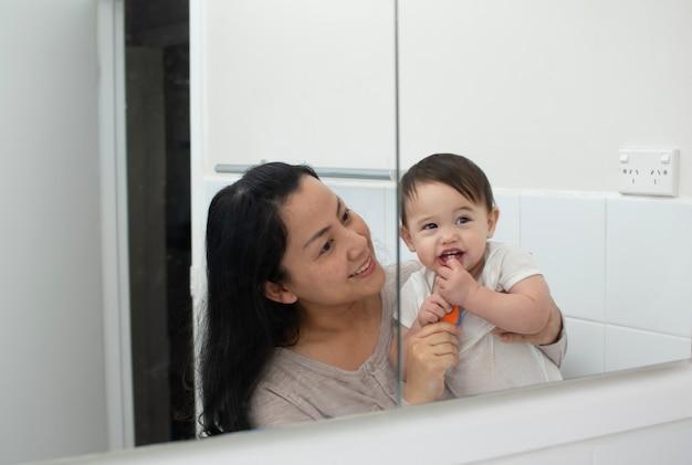 Mère enseigne à son fils le pinceau de ses dents