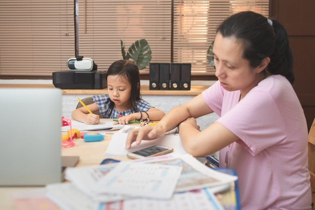 Mère l'enseignement des devoirs et parler avec sa fille pour étudier et faire des affaires travaillant à domicile