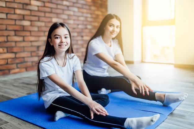 Mère enseigner à sa fille comment s'asseoir dans les papillons de yoga pose à la maison. lumière du soleil.