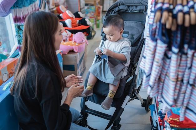 La mère essaie d'adapter le produit à son fils avant de l'acheter