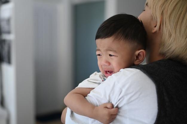 Mère essayant de calmer son bébé qui pleure tout en se tenant dans une maison confortable.