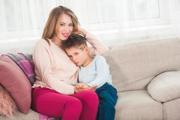 Mère essayant de calmer son petit fils. maman embrassant son enfant à la maison