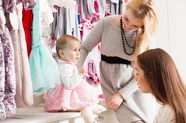 Mère essayant de mettre sa petite fille chaussettes dans un magasin de vêtements