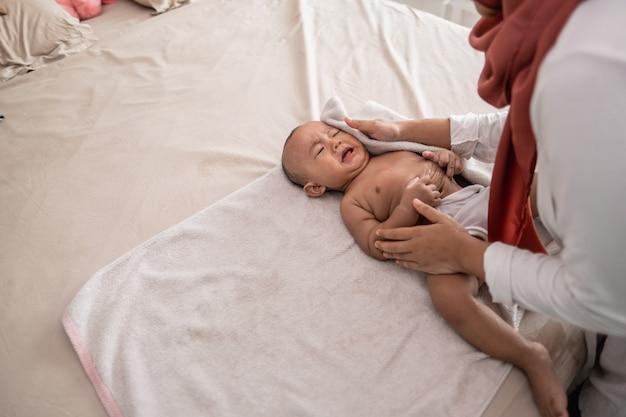 Mère essuie son petit garçon avec une serviette