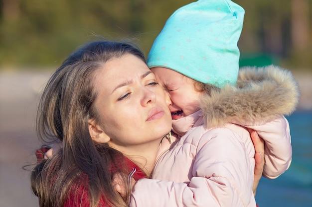 Mère étreignant pleurer bouleversé petite fille. femme inquiète tenant une fille triste malheureuse.