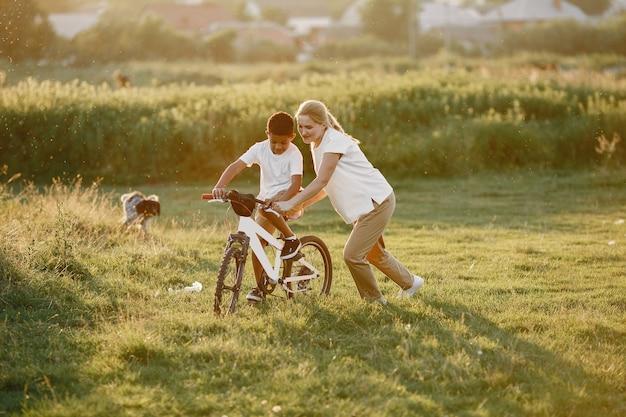 Mère européenne et fils africain. famille dans un parc d'été. enfant à vélo.