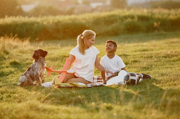 Mère européenne et fils africain. famille dans un parc d'été. des gens assis sur la couverture.
