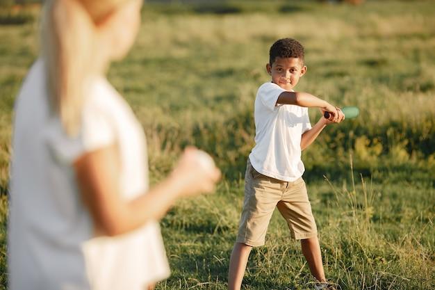 Mère européenne et fils africain. famille dans un parc d'été. les gens jouent avec morsure et balle.
