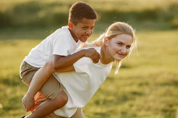 Mère européenne et fils africain. famille dans un parc d'été.