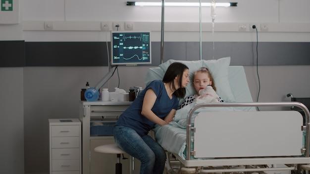 Mère expliquant le traitement médicamenteux à sa fille malade après avoir subi une chirurgie médicale