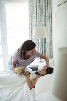 Mère faisant dormir sa fille dans la chambre