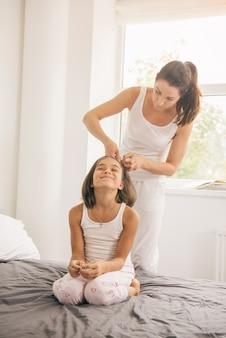 Mère faisant des tresses à sa fille