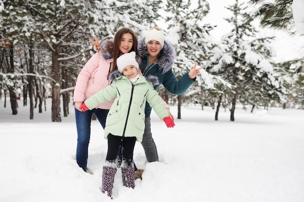 Mère de famille et deux filles s'amusent et jouent sur fond d'arbres enneigés et de forêts. plaisirs d'hiver