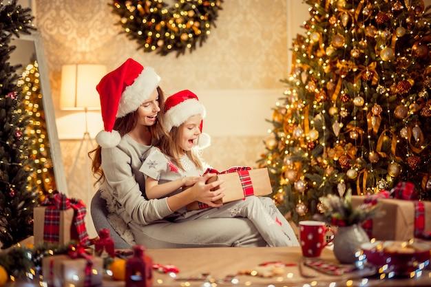 Une mère de famille heureuse et son enfant emballent des cadeaux de noël
