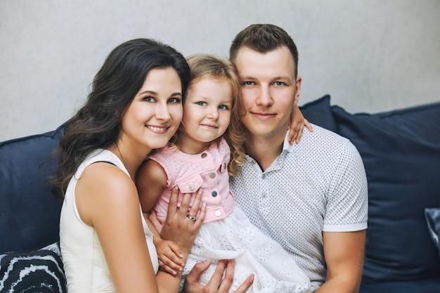 Mère de famille, père et fille heureuse et belle avec des sourires à la maison portrait ensemble