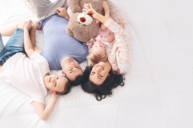 Mère de famille père fils et petite fille à la maison ensemble heureux allongé sur la vue de dessus de lit