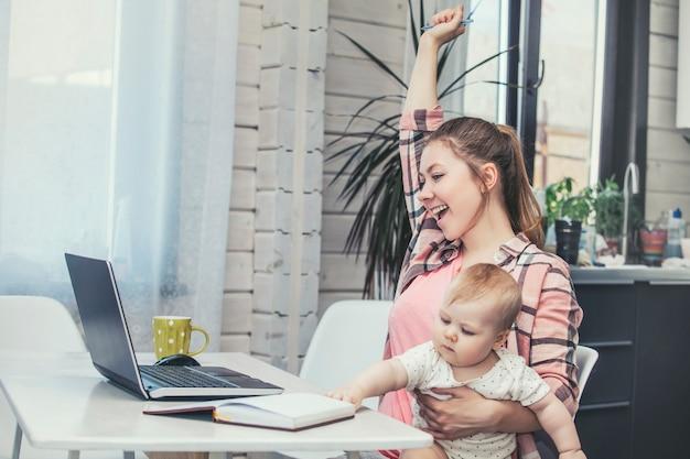 Mère de famille travaille avec un ordinateur portable via internet et le bébé heureux ensemble à la maison en souriant