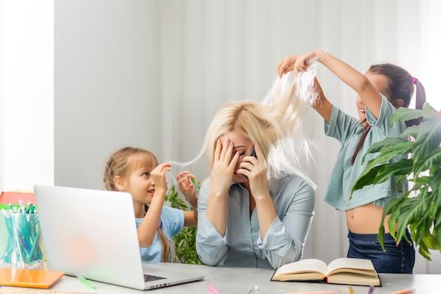 Mère fatiguée avec des enfants jouant alors qu'elle est épuisée