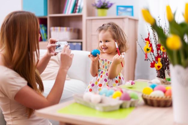 Mère fière de prendre une photo de sa fille avec un œuf de pâques