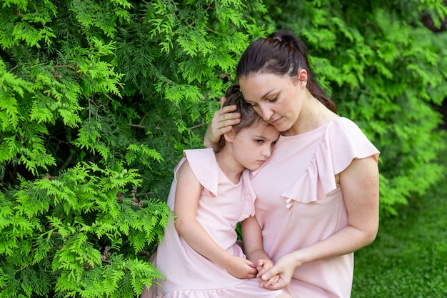 Mère et fille 5-6 ans marchant dans le parc en été, fille et mère riant sur un banc, fête des mères